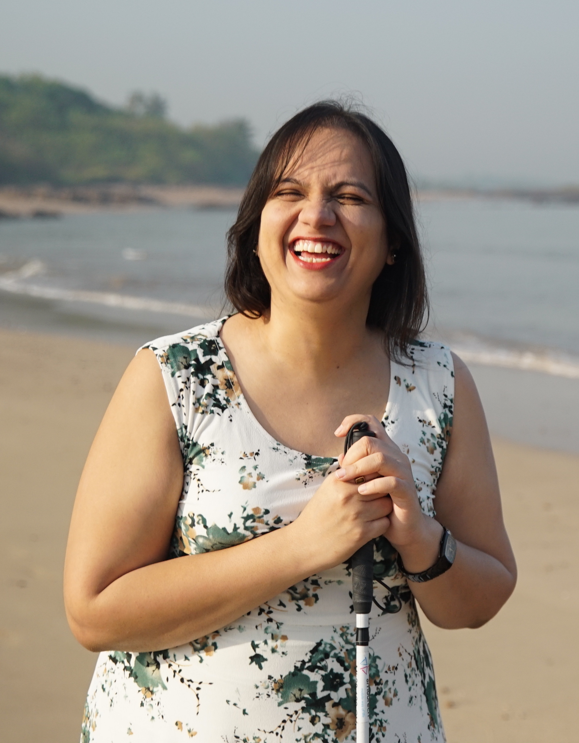 Nidhi Goyal standing on the beach with her cane. She is wearing a white sleevless dress and is smiling at the camera. We can see the waters behind her.