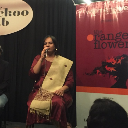Orange Flower Summit - Mumbai - December - 2017: Nidhi is sitting on the stage, speaking into the microphone. On her left, there is a banner, the top half is deep red in color and the bottom half is white. Separating the two is an orange band. On the red color, the words 'The orange flower' is written. Below this is a silhouette of a girl's face in side profile, with black and orange leaves for hair. On Nidhi's right, Lalita Iter is sitting. In the background there are black curtains and on the top left corner, on a light brown board the words: The cuckoo club are written.