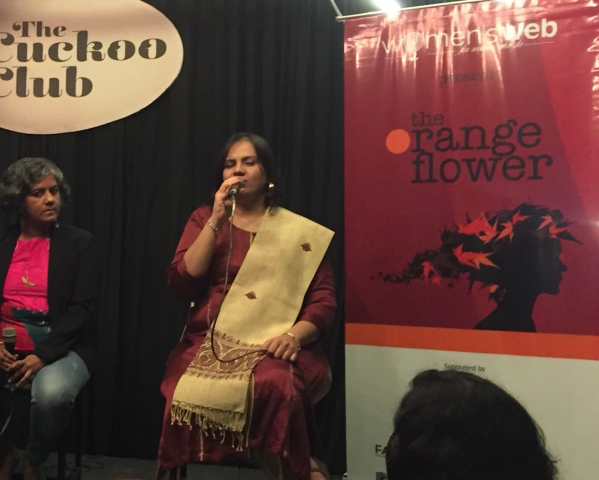 Nidhi is sitting on the stage, speaking into the microphone. On her left, there is a banner, the top half is deep red in color and the bottom half is white. Separating the two is an orange band. On the red color, the words 'The orange flower' is written. Below this is a silhouette of a girl's face in side profile, with black and orange leaves for hair. On Nidhi's right, Lalita Iter is sitting. In the background there are black curtains and on the top left corner, on a light brown board the words: The cuckoo club are written.