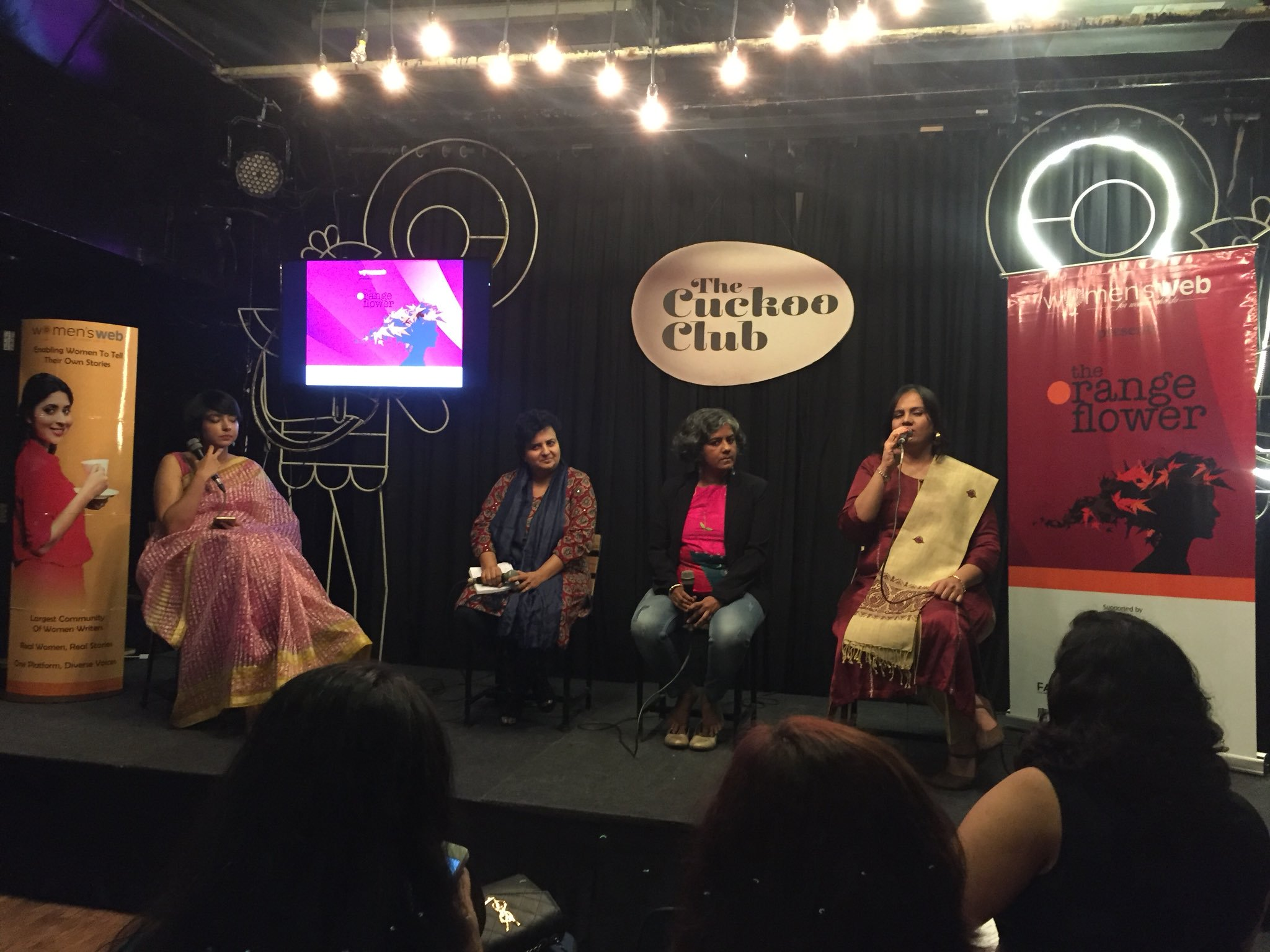"Four women are sitting on chairs on a black stage and in the background there are black curtains. On a light brown oval shaped board, the words: The Cuckoo Club"" is written. There is a television screen on a stand on the left side. A woman with short hair and a pink saree is sitting beside the television, on her right is Dr. Shilpa Phadke, on her right is author Lalita Iyer and on the extreme is Nidhi Goyal, speaking into the mic. From the audience, the backs of 3 women are visible. On the extreme right there is a banner which is red and white in color and has the words ""Orange Flower Summit"" and the silhouette of a woman's side profile face and neck."