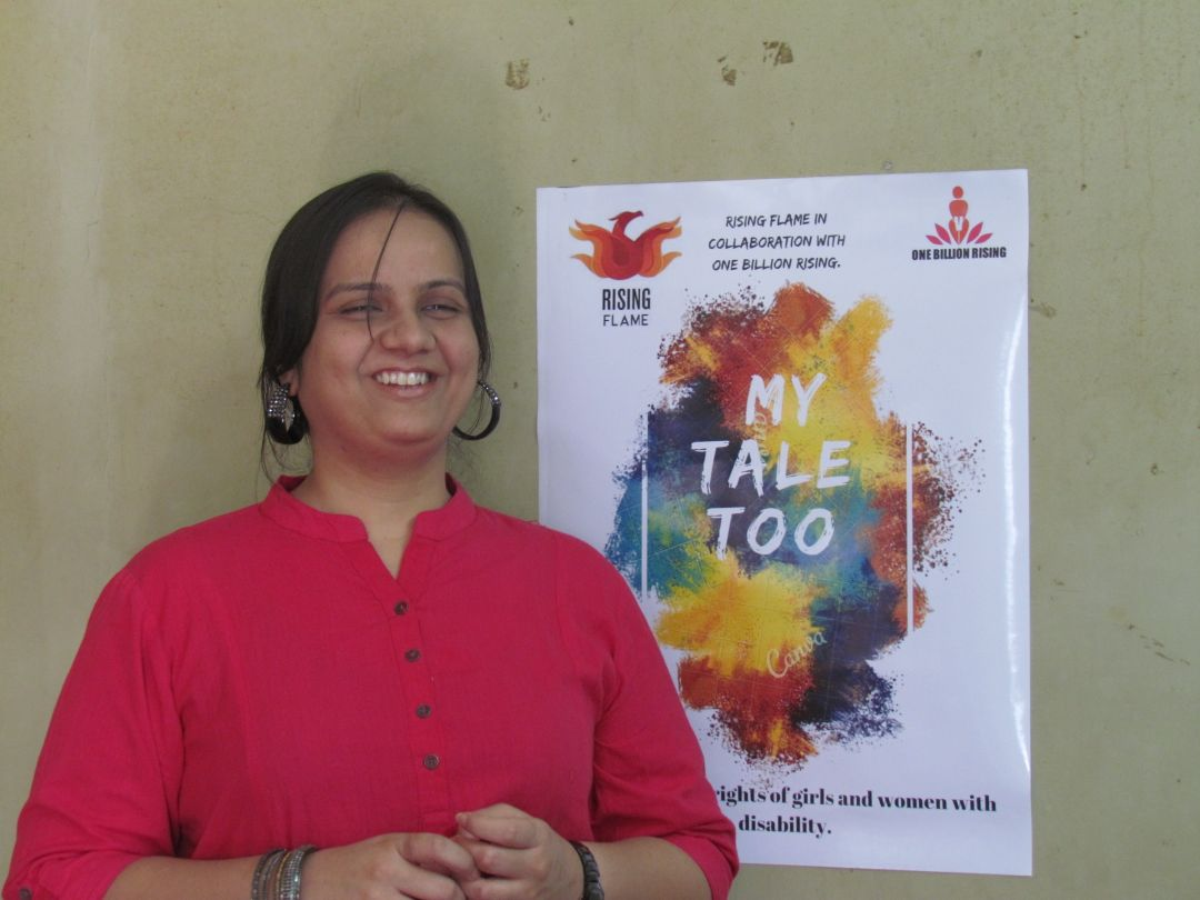 Nidhi standing next to the My Tale too poster which is stuck on the wall. She is wearing a pink kurta and black hoop earrings.