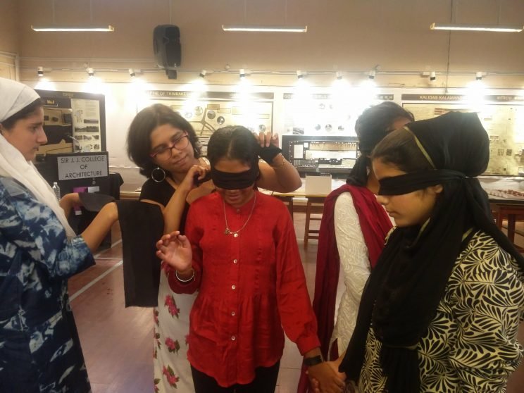 Tour in the Dark - Mumbai - February - 2018: This is an image from our event, Tour in the dark. Two women are blindfolded, another woman is tying the blindfold for another woman. There is another girl who is holding the black cloth in her hands.