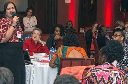 Money and Movements - Kenya - April - 2018: On the left, Nidhi is standing up and speaking into a mic, addressing a room full of people. There are 11 other people in the photo sitting around round tables listening to the speaker. People are from diverse nationalities. In the background there is a speaker in front of a red wall