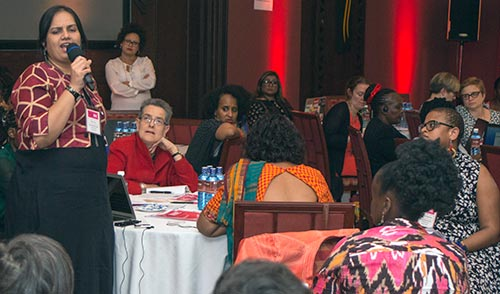 On the left, Nidhi is standing up and speaking into a mic, addressing a room full of people. There are 11 other people in the photo sitting around round tables listening to the speaker. People are from diverse nationalities. In the background there is a speaker in front of a red wall