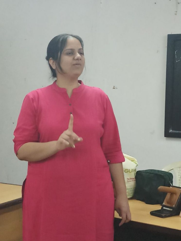 NAB-Mumbai-April-2018: Nidhi Goyal is standing and talking. She is wearing a pink kurta and has her index finger pointing up.