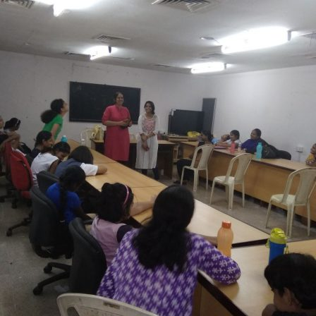 NAB-Mumbai-April-2018: Nidhi Goyal and Pooja Menon are standing in front of a classroom and addressing a room full of children and women who are sitting around rectangular conference tables. There around 12 people in the room.
