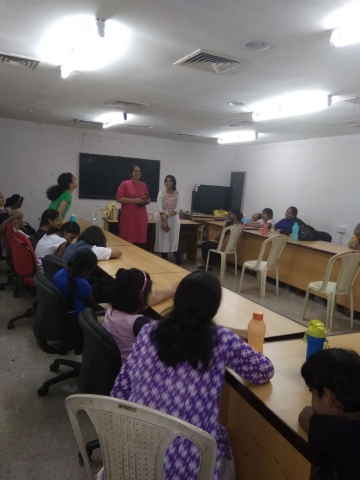 Nidhi Goyal and Pooja Menon are standing in front of a classroom and addressing a room full of children and women who are sitting around rectangular conference tables. There around 12 people in the room.