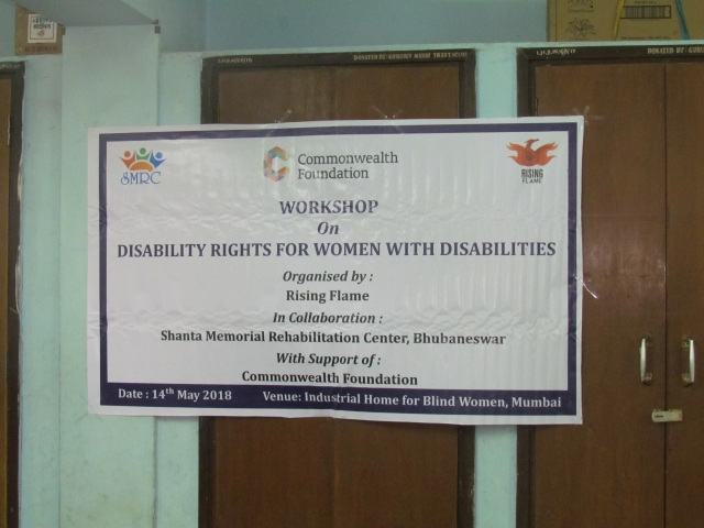This is a photo of a banner which has been put up across two doors. The banner is white with a black outline. The SMRC logo is on the left side, in the middle it is the Commonwealth foundation and on the right is the Rising Flame logo. It has the following text: Workshop on Disability Rights for Women with Disabilities. Organised by Rising Flame in collaboration with Shanta Memorial Rehabilitation Center, Bhubaneswar with support of Commonwealth foundation