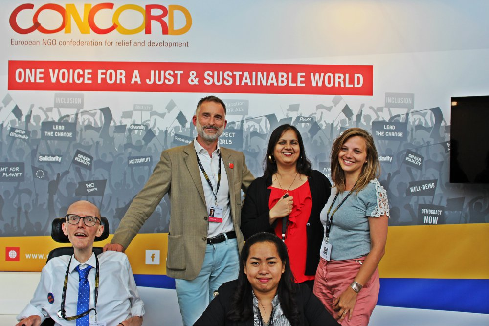 EDD - Brussels - June - 2018: 5 people, 2 men and 3 women are in front of a hoarding which has the following words: Concord (in yellow and red). European NGO confederation for relief and development. One Voice for a just and sustainable world. There are silhouettes of people holding banners on the hoarding. A man in a brown jacket, Nidhi in a red top and another woman in a light blue shirt are standing with arms around each and in front of them is a woman in a black jacket is on a wheelchair and on the left is a man is light blue shirt is on a wheelchair. They are all posing for the camera.