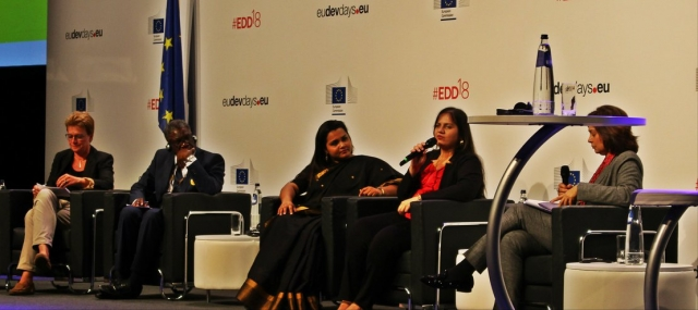 Five people, 1 man and 4 women are sitting in front of a large whiteboard on a stage. The board has the following written: #EDD18, eudevdays.eu and a logo. This is spread all over the board. Nidhi is sitting second from the right in a red shirt and black jacket. She is holding the microphone and addressing an audience. The woman on her right is in a grey pant suit, the woman on her left is wearing a black saree, a man sitting next to the lady in the saree is in a dark blue pant suit and the lady on the extreme left is in beige pants and a black top and jacket.