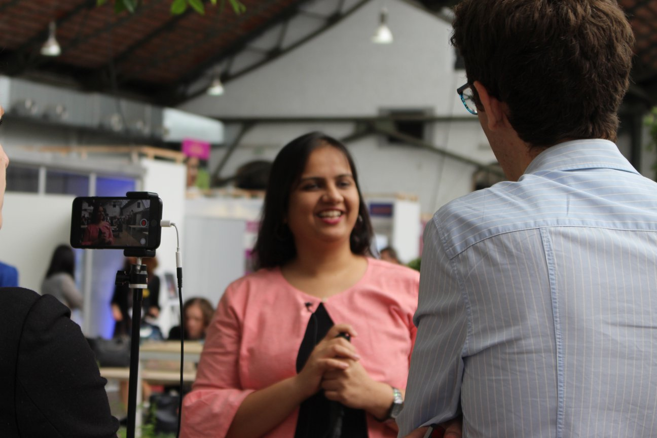 There are two people in focus, a man's back who seems to be talking to Nidhi. Nidhi in a light pink top is looking at the man and holding her cane. On the left, there is a phone attached to a stand.