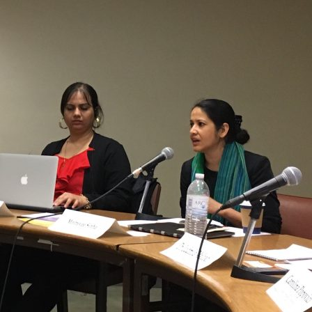COSP - USA - June - 2018: Nidhi along with another woman are seated at a conference table. Nidhi is wearing a red top and a black jacket with golden hoop earrings. She is looking down and her hand is on her laptop which is in front of her on the table. The woman next to her is wearing a black and green scarf; her hair is tied up in a bun and she is talking into a microphone which is kept on the table. The table has name tags, mics and a water bottle.