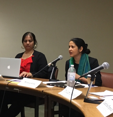 Nidhi along with another woman are seated at a conference table. Nidhi is wearing a red top and a black jacket with golden hoop earrings. She is looking down and her hand is on her laptop which is in front of her on the table. The woman next to her is wearing a black and green scarf; her hair is tied up in a bun and she is talking into a microphone which is kept on the table. The table has name tags, mics and a water bottle.