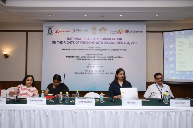 4 people, 3 women and 1 man sitting at a panel table. Nidhi is sitting 2nd from the right working on her laptop. The table has name tags, water bottles and microphones. Behind them is a large hoarding with the following words: National Disability Consultation on the Rights of Persons with Disabilities Act, 2016. Organised by National Centre for Promotion of Employment for Disabled People.