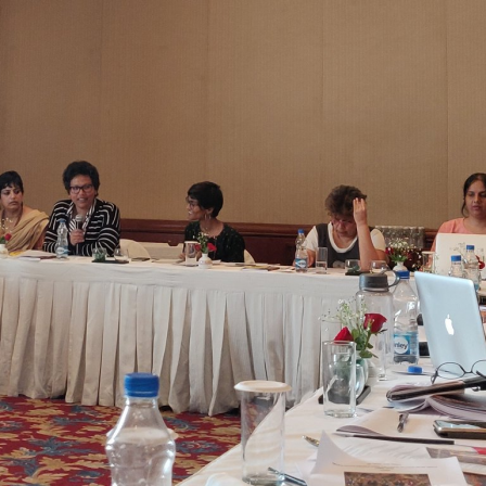 My Troll, Our Troll - India - November - 2018: There are 5 women sitting at a rectangular conference table which is covered in white tablecloth. Nidhi is sitting on the extreme right wearing peach and looking down into her laptop with one earphone in her left ear. One of the women is talking into a hand microphone.