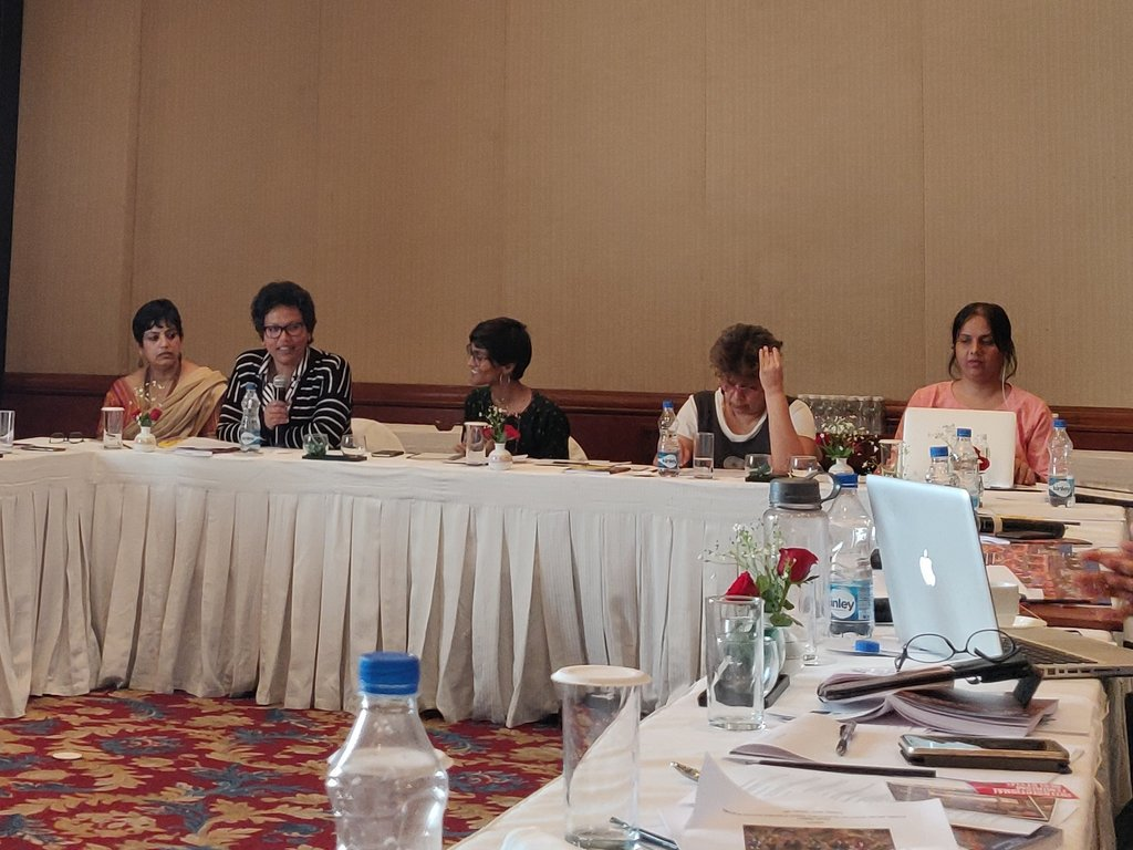 There are 5 women sitting at a rectangular conference table which is covered in white tablecloth. Nidhi is sitting on the extreme right wearing peach and looking down into her laptop with one earphone in her left ear. The women are of diverse nationalities and one of them is talking into a hand microphone.