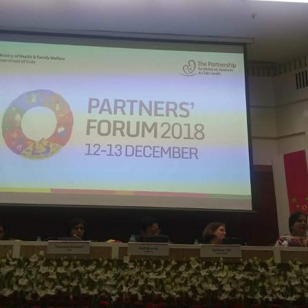 Partners' Forum - Delhi - December - 2018: Most of the image is a screen with a white background on which on the left side it is written: Ministry of Health and Family Welfare, Government of India. On the right it is written, The Partnership for Maternal, Newborn and Child Health. At the centre is a logo and beside that it is written, Partners' Forum 2018 12-13 December. Below the screen, six people are sitting at a panel. Nidhi is sitting on the extreme right and is speaking into the microphone. Below the panel table there is a row of white flowers.