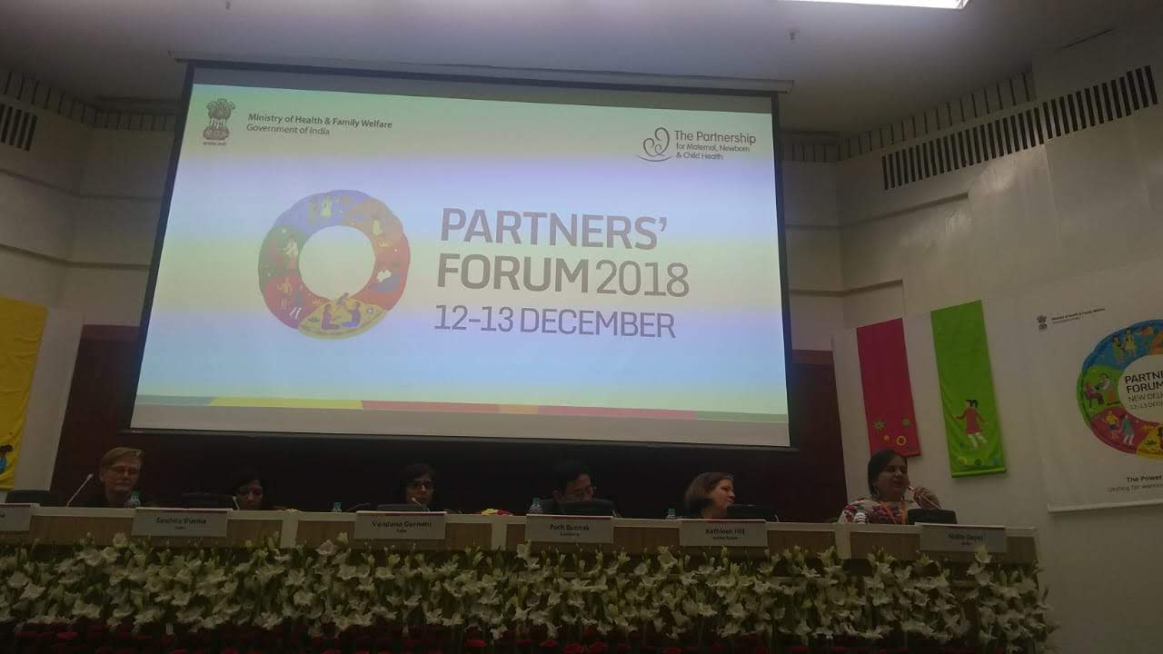 Most of the image is a screen with a white background on which on the left side it is written: Ministry of Health and Family Welfare, Government of India. On the right it is written, The Partnership for Maternal, Newborn and Child Health. At the centre is a logo and beside that it is written, Partners' Forum 2018 12-13 December. Below the screen, six people are sitting at a panel. Nidhi is sitting on the extreme right and is speaking into the microphone. Below the panel table there is a row of white flowers.