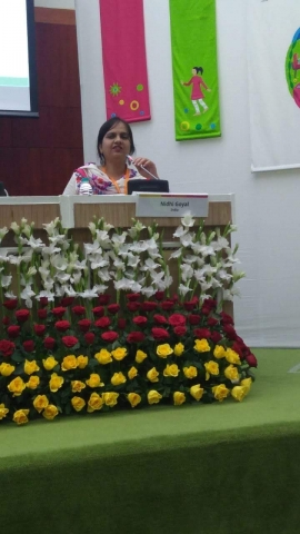 Nidhi is sitting behind a table and speaking into the microphone. In front of is her name tag and in front of the table there is a row white flowers, below that there is a row of red flowers and below that there is a row of yellow flowers. Behind Nidhi there are two vertical flags hanging, one is pink in colour and the other is green.