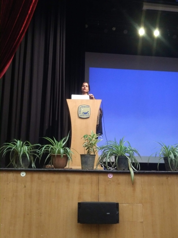 Nidhi is standing behind a podium and speaking into the microphone. The podium is on a stage. In the background there is a very big screen. Behind Nidhi are black curtains for the wings and in front of the podium, at the edge of the stage are potted plants in a row. Attached to the wall of the stage is a speaker.