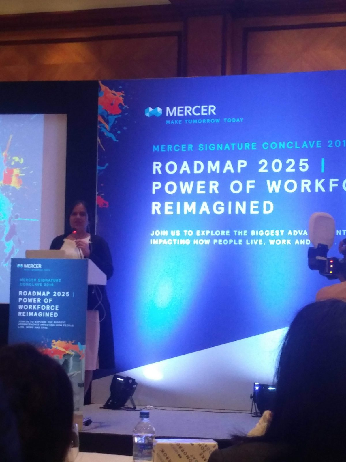 Mercer Keynote Address-Mumbai-December-2018: Nidhi goyal is speaking at podium in a white and black dress with a black jacket. Behind her, there is a huge hoarding in blue with the Mercer logo on the top left and below that it is written: Mercer Signature Conclave 2018. Roadmap 2025 Power of Workforce Reimagined.