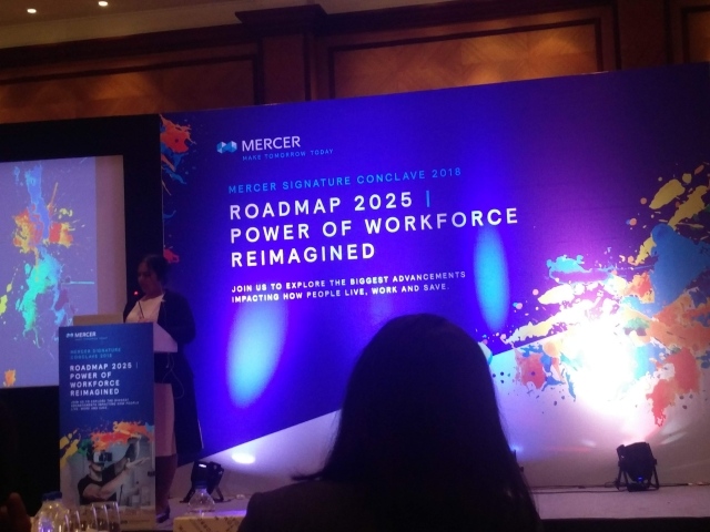 Nidhi goyal is speaking at podium in a white and black dress with a black jacket. Behind her, there is a huge hoarding in blue with the Mercer logo on the top left and below that it is written: Mercer Signature Conclave 2018. Roadmap 2025 Power of Workforce Reimagined.