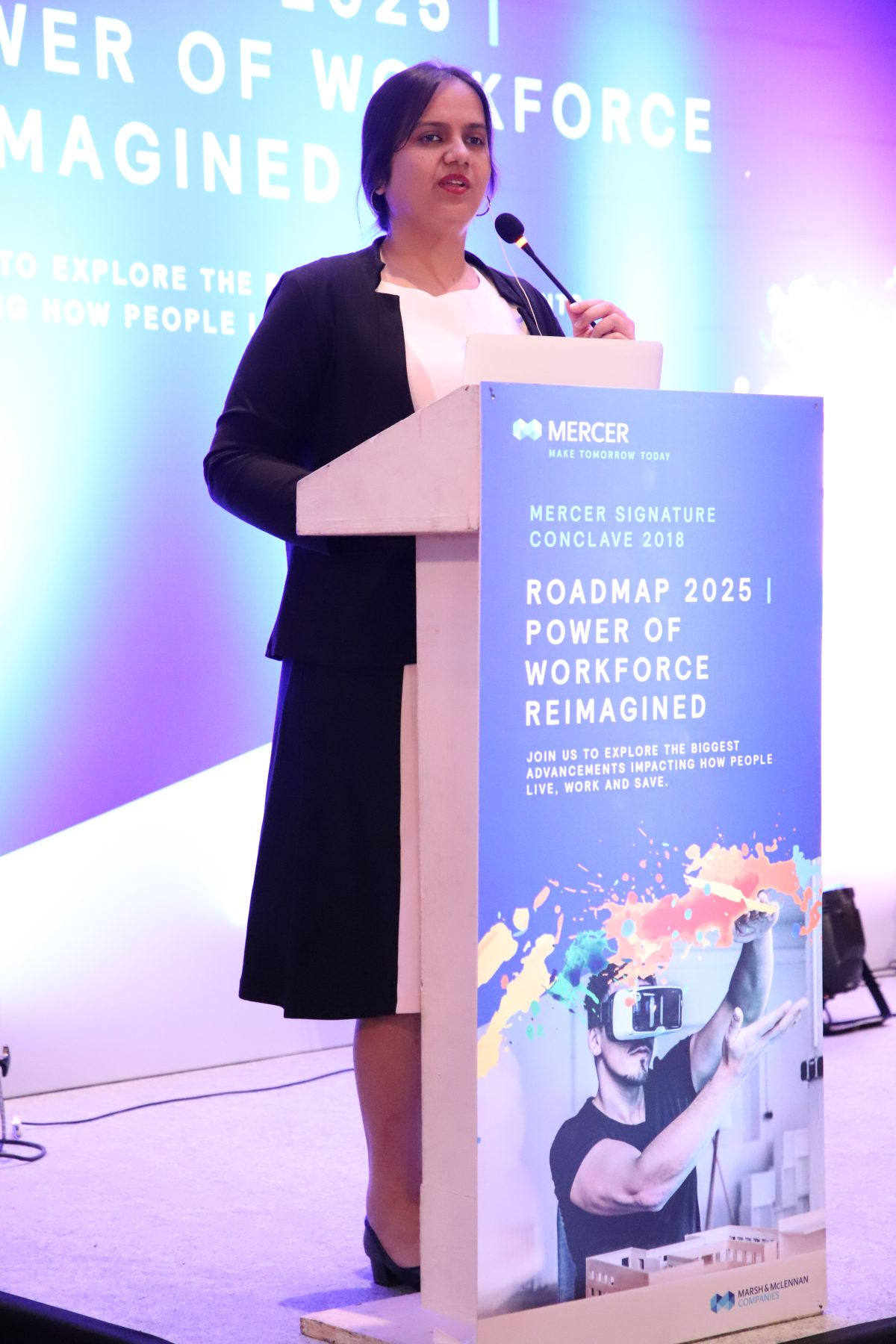 Mercer Keynote Address-Mumbai-December-2018: A full length image of Nidhi standing and speaking behind a podium. She is wearing a white and black dress and a black jacket. The podium is blue in colour and has the following words written on it: Roadmap 2025 Power of Workforce Reimagined.