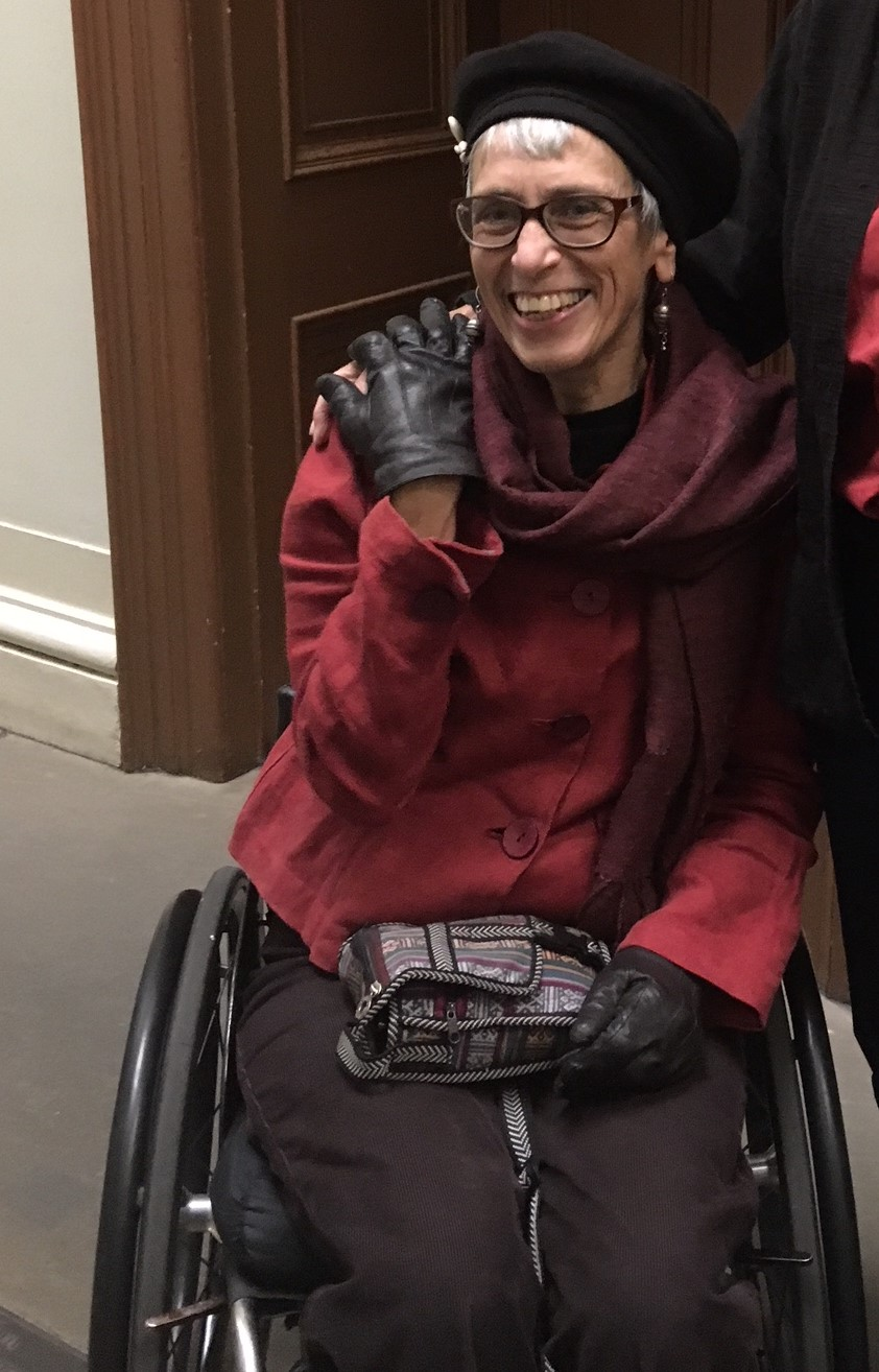 Janet is sitting on her wheelchair wearing a red cardigan and a black cap. She has black gloves on. She is wearing glasses and is smiling at the camera.