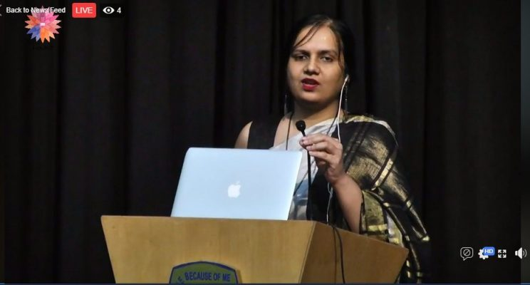 World Congress on bioethics - Bangalore - December - 2018: Nidhi is speaking into a microphone and she is standing behind a podium. Her laptop is kept in front of her on the podium. She is wearing a black saree which is a combination of light grey, black and golden. She has her earphones in her left ear. On the top left corner is the logo for the World Congress on bioethics.