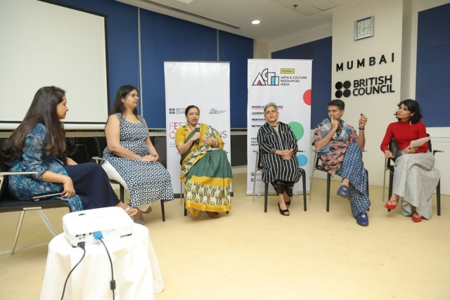 nidhi goyal along with Anisha shah, brinda miller, parmesh shahani and moderator Rashmi dhanwani. in a room with blue walls and a projector screen behind them