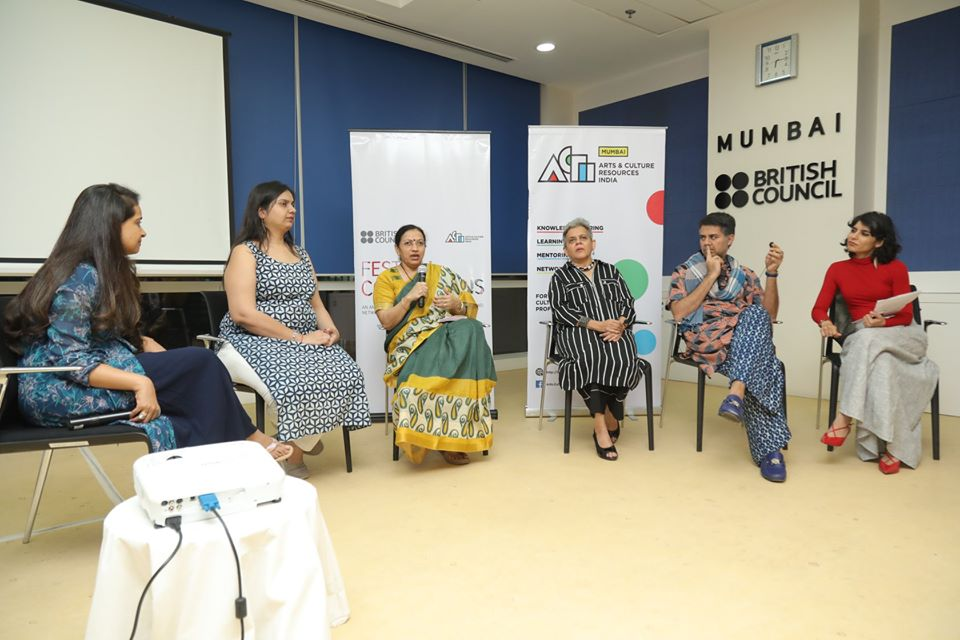 nidhi goyal along with Anisha shah, brinda miller, parmesh shahani and moderator Rashmi dhanwani. in a room with blue walls and a projector screen behind them