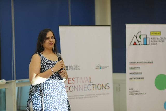 nidhi goyal holding a mic and speaking at the art x festival connections event. behind her are two white standees - one says british council festival connections and the other says arts and culture resources of india
