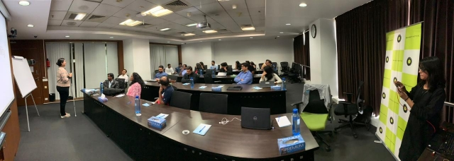 at the training at Ola office in bangalore- a panoramic image of the room. Nidhi standing in the front . a projector screen behind her. The audience sitting and listening