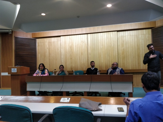 a panel of 4 people- left to right- nidhi goyal, prof. rachna johari, hardeep singh and abhishek annica. sign language interpreter on the right. a podium on the left of the panel