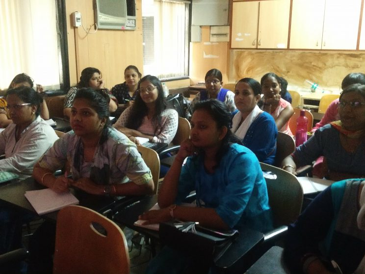 Training at TISS - Mumbai - November - 2018: Around 13 women are sitting on chairs in a room. They are listening to someone speak. Few of them are writing notes in a book.