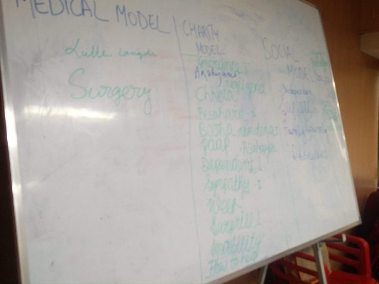 Training at TISS - Mumbai - November - 2018: There is a white board with three columns written on it. The medical model, Charity model and social model. There are more words under three models.