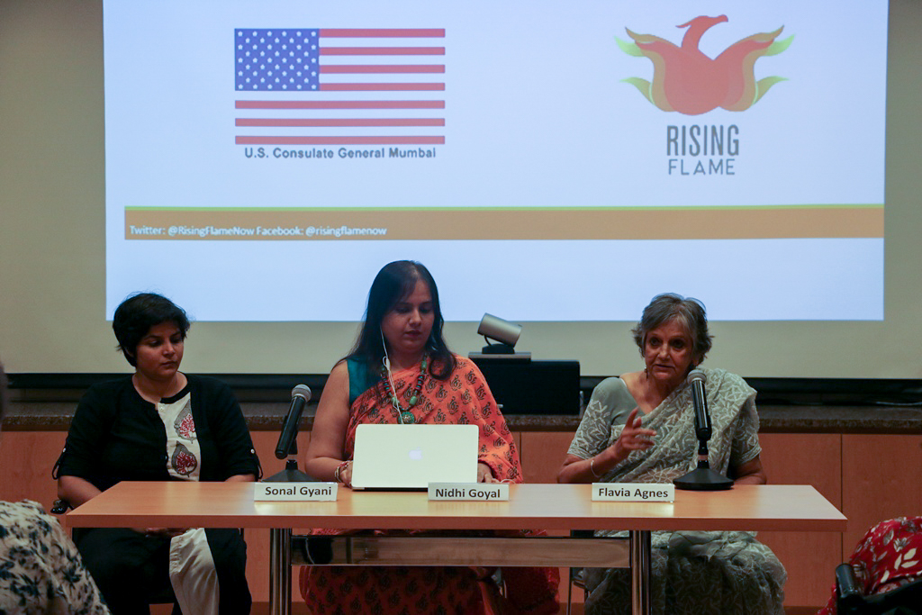 Sonal Giani, Nidhi Goyal and Flavia Agnes are sitting at a table. Flavia is addressing an audience. In the background, there is a large screen with the two logos of the consulate and Rising Flame.