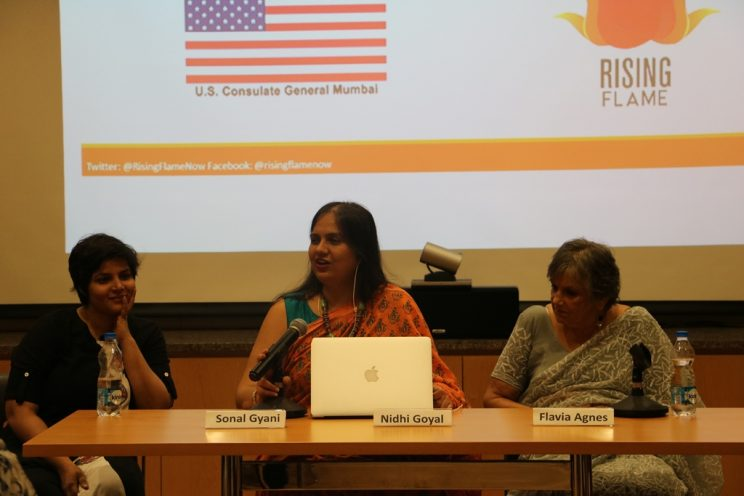 Voices-Mumbai-December-2018: Sonal Giani, Nidhi Goyal and Flavia Agnes are sitting at a table. Nidhi is speaking into the microphone and in the background, there is a large screen which has the logos of the U.S consulate General and Rising Flame.
