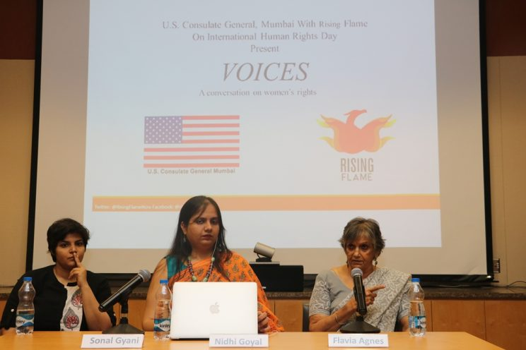 Voices-Mumbai-December-2018: Sonal Giani, Nidhi Goyal and Flavia Agnes are sitting at a table. Flavia is addressing an audience. In the background, there is a large screen with the following words: U.S Consulate General Mumbai with Rising Flame On International Human Rights Day Present VOICES, a conversation on women's rights. At the bottom are the two logos of the consulate and Rising Flame.
