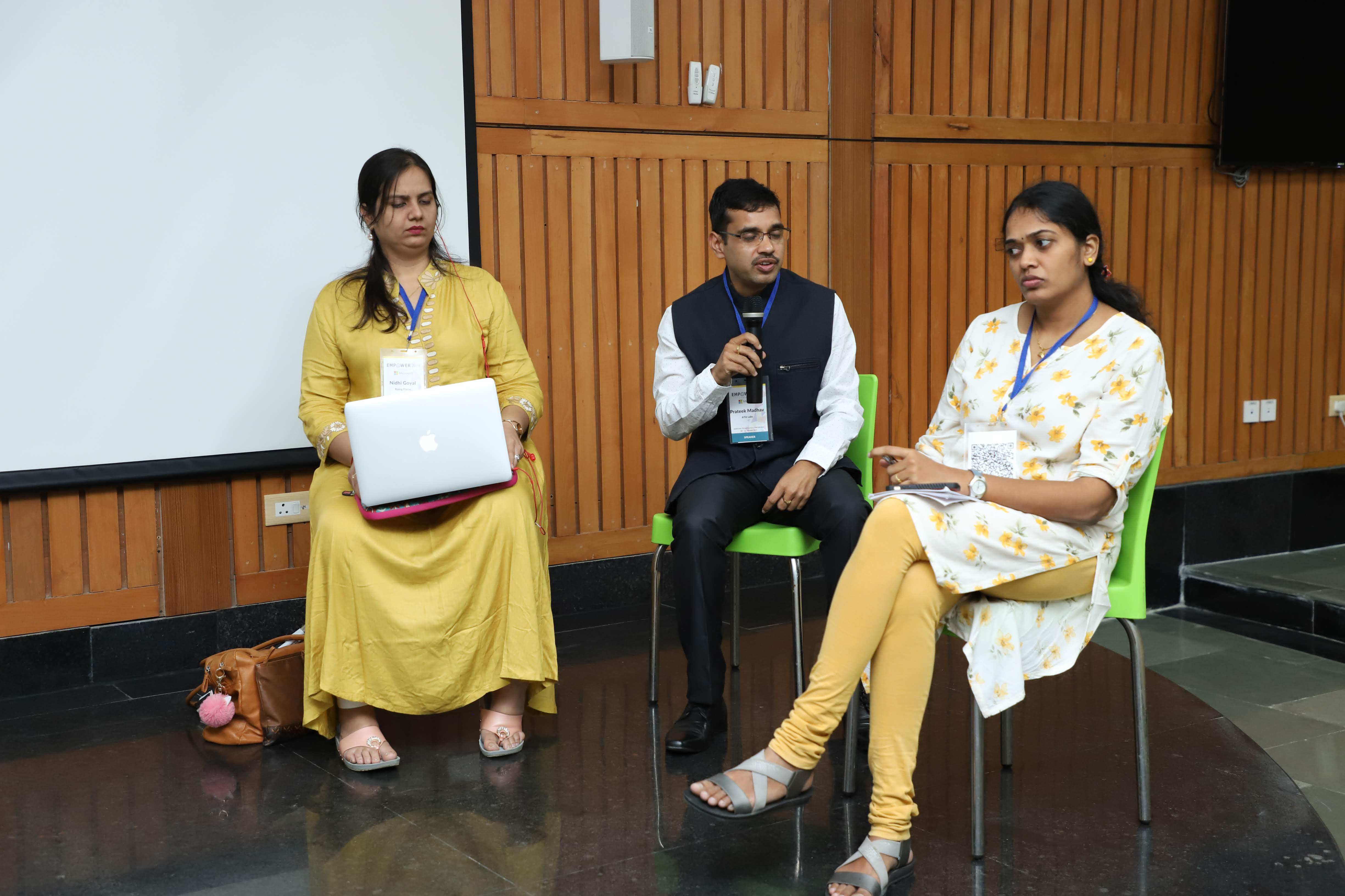 nidhi goyal along with two other panelists at empower 2019 at IIT delhi. the wall has wooden panels and a projector screen