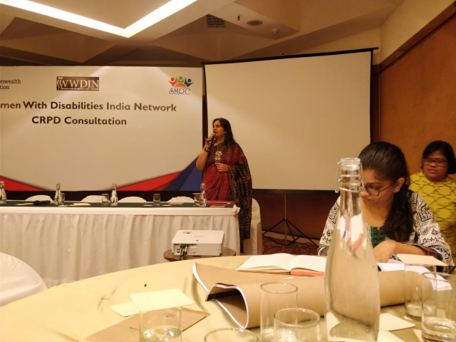 nidhi goyal speaking at women with disabilities india network crpd consultation. participants sitting around tables and writing