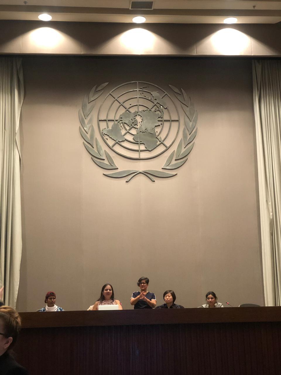 nidhi on a panel with smitha sadasivan, jing and rama dhakal. the UN logo behind them. sign language interpreter standing behind them