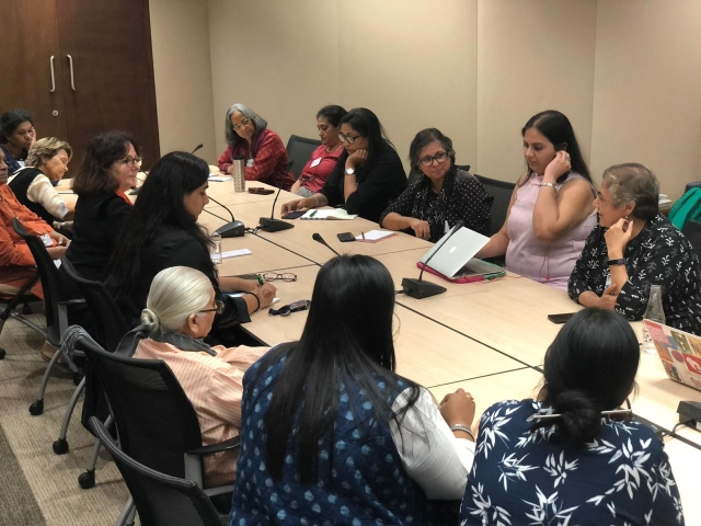 Nidhi in a meeting with activists. Suneeta Dhar sitting beside her. they're sitting around a rectangular table , writing notes on their laptops and notepads
