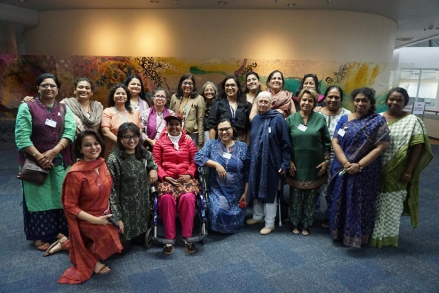group photo at the asia pacific beijing + 25. disabled and non disable women, including nidhi goyal and smitha sadasivan standing together, smiling.