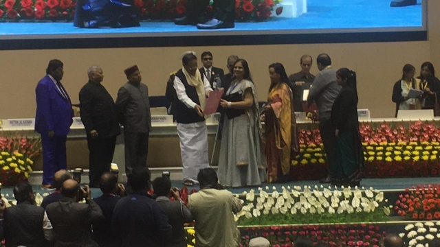 nidhi goyal recieving the national award for the empowerment of persons with disabilities by the vice president of india, Venkaiah Naidu. dignitaries such as Shri Thaawarchand Gehlot, Hon'ble Union Minister of Social Justice & Empowerment, Shri Krishan Pal Gurjar, Hon'ble Minister of State for Social Justice & Empowerment, Shri Ramdas Athavale, Hon'ble Minister of State for Social Justice & Empowerment, Shri Rattan Lal Kataria, Hon'ble Minister of State for Social Justice & Empowerment present on stage. stage decorated with flowers and photographers in the front taking pictures of the ceremony