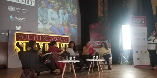 a panel of five women - founder and executive director rising flame nidhi goyal, Jasmine George from Hidden Pockets, M Suman – a trans rights advocate from Bangalore, and Dr Zoya Rizvi from the Ministry of Health and Family Welfare. moderator - journalist and #MeToo activist Rituparna Chatterjee.. behind them, the board says Youth ki Awaaz summit. A screen above the board with a picture of smiling people