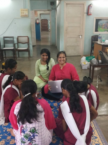 Pooja Menon and Nidhi Goyal are in conversation with few people. Pooja is wearing a green kurta and Nidhi is in a red kurta while holding a laptop. They are talking to to four school children and a woman in a pink kurta. They are in a room with few chairs and a table. They are smiling.