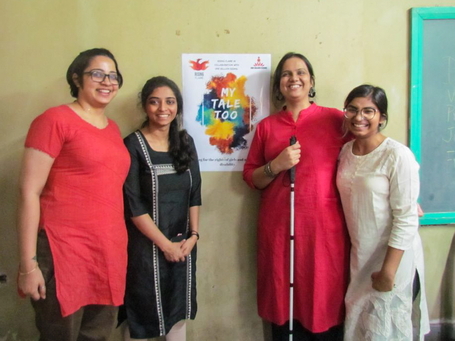 Team Rising Flame comprising Srinidhi, Pooja Menon, Nidhi Goyal, and Malavika Goyal are standing in front of the workshop poster with the words 'My Tale Too'
