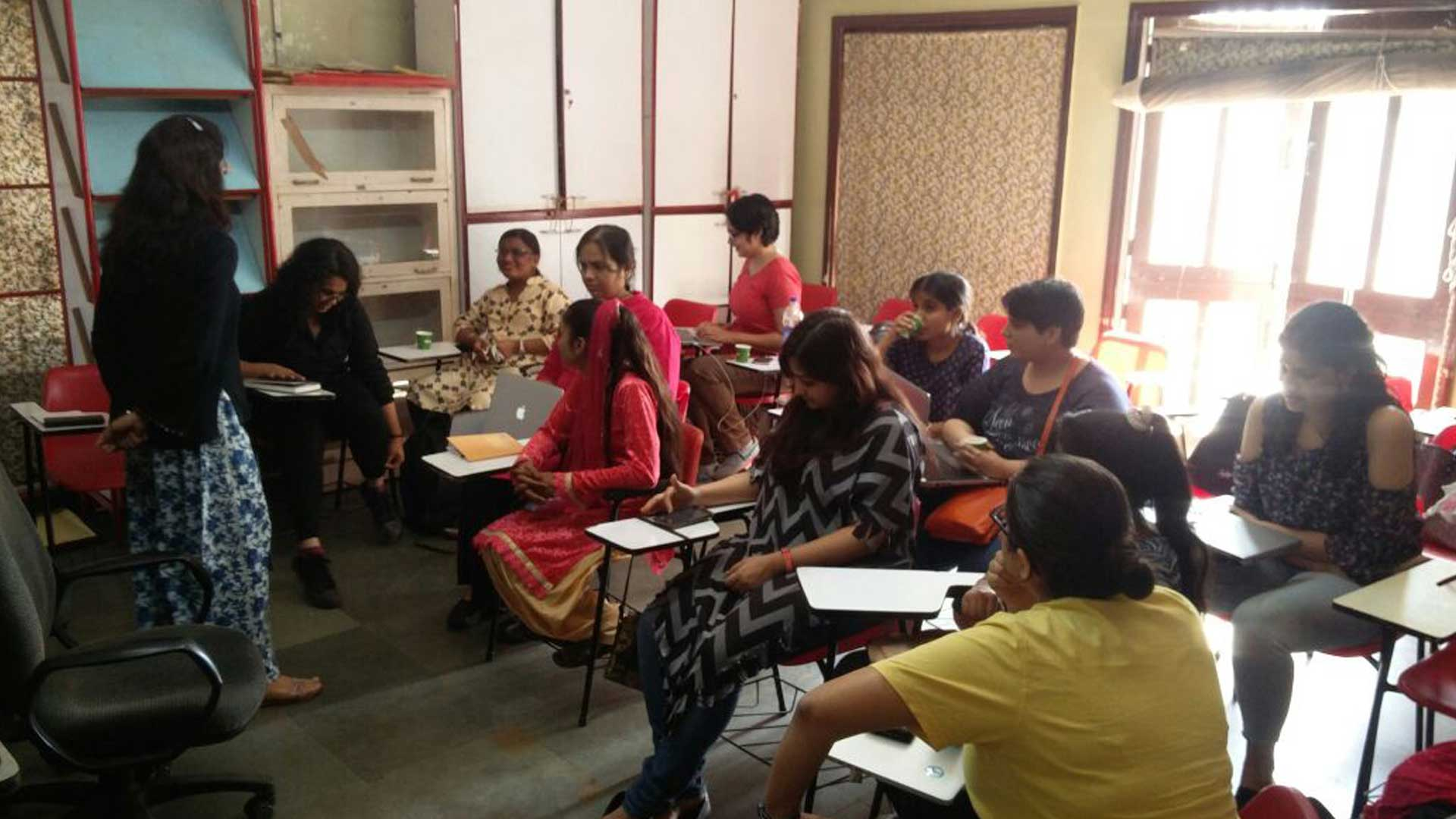It is a classroom setting, with red chairs which have attached side tables. Around 12 women sitting in the room, facing the front. One woman in a black kurta and white and blue printed pyjamas is addressing the room and everyone else is listening to her. One blind woman is drinking from a paper cup. One woman in a pink kurta is looking down and has her laptop open. One woman sitting in the front row is looking into her phone. There is sunlight coming in from the back of the room and there are cupboards on the right hand wall.