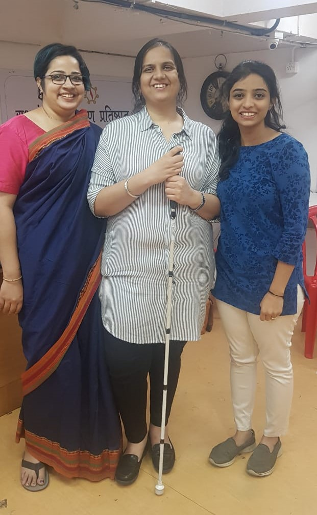 On the left is Srinidhi in a Blue Saree with a pink blouse and border. In the center is Nidhi in a white Tunic with grey stripes an black pants. On the right is Pooja in a Blue Tunic and beige pants. All three are smiling.